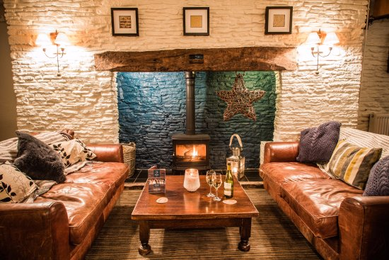 Nibley, UK: Cosy sofas and fireplace.