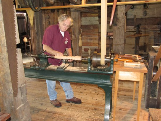 Pittsfield, MA: Tour guide demonstrating wood lathe, belt driven from water turbine shaft.