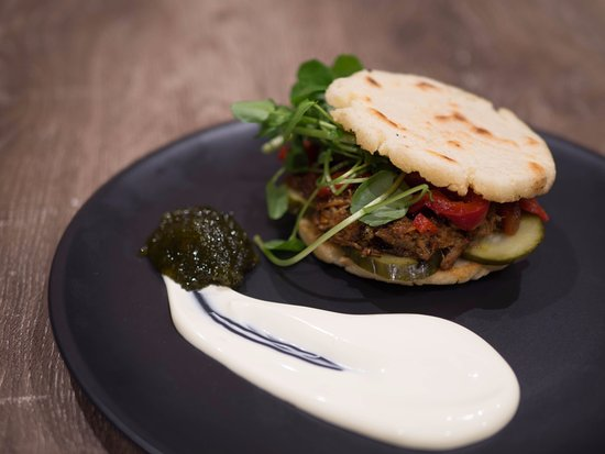 Fitzroy, Australia: Corn bread arepa w/ pulled pork, marinated capsicums, watercress and dill pickles