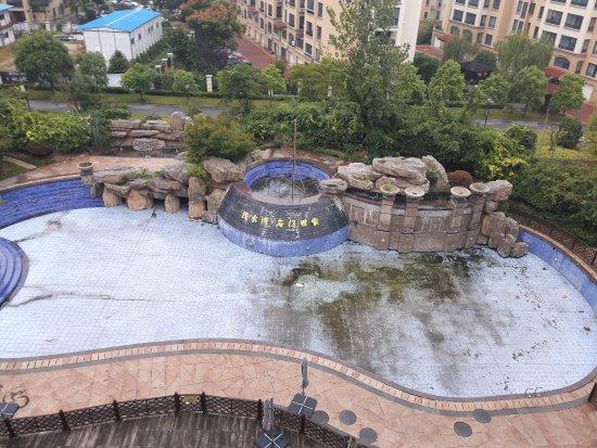 Rudong County, China: Utsikt från rummetn. Avstängd smutsig pool tråkigt