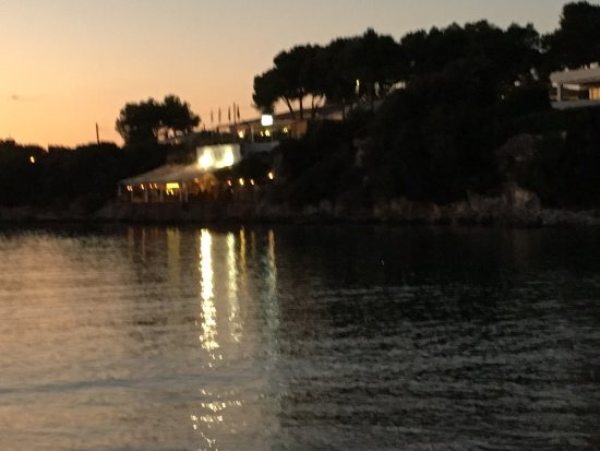 Cova Sa Nacra: Sunset view of the restaurant from Cala Santandria
