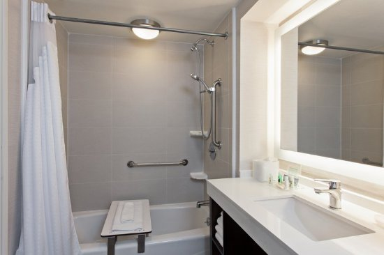 ADA bathroom has tub with shower seat and grab bars. - Picture of ...