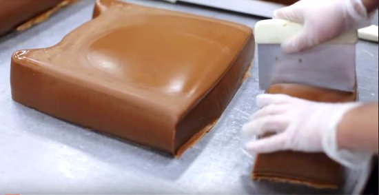 Clinton Township, MI: a candy maker cuts a 40lb block of Sanders real caramel