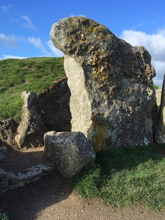 """Avebury, UK: The large stone outside the entrance showing the """"unguarded drop from the top of the barrow"""""""