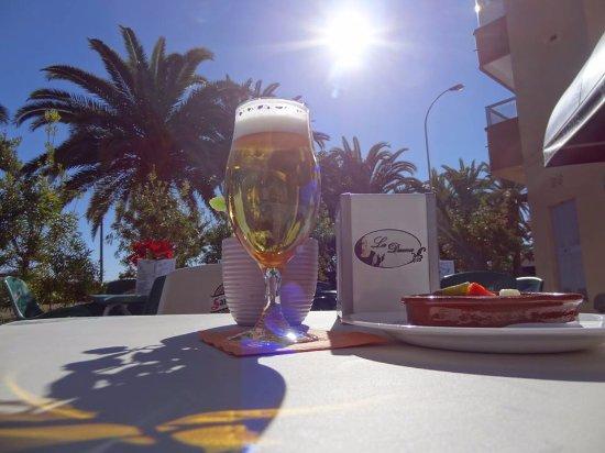 La Dama Algarrobo Costa en la Terraza con cerveza y tapas.