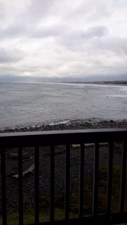 Lanai at the Cove: Standing at the slider to the little balcony. The black things in the ocean are surfers.