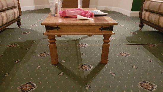 Menstrie, UK: Upgrade room.Table with bent legs just by the gaps in the carpet.