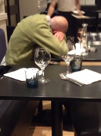 Agen, Frankrijk: Intoxicated man , shoes off and teeth on the chair. Not something to enjoy your meal with!