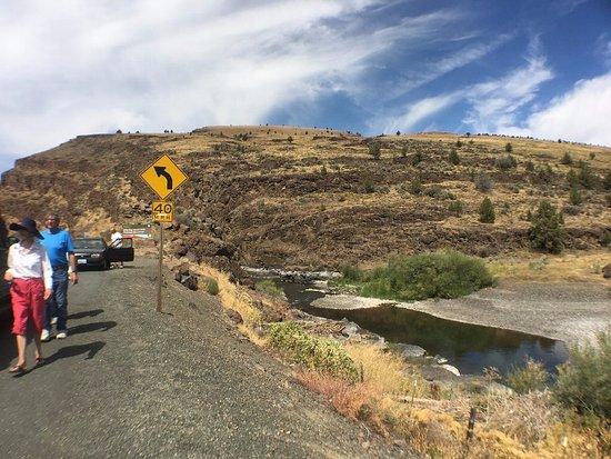 John Day Fossil Beds National Monument: 画面左が道路で標識の向こうから河原に下ります。川はジョンディ川です。