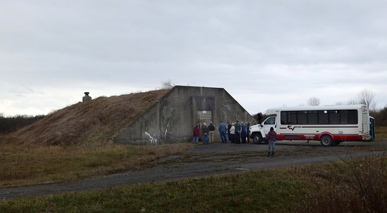 Romulus, NY: A tour bus stops at one of the 519 massive earth-covered weapons storage igloos on a White Deer