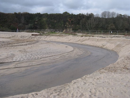 St Austell, UK: Stream across beach and 'building' site in the background!