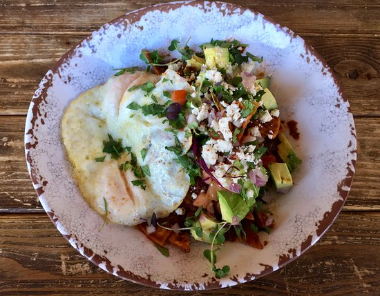 What a Dish Cafe & Catering: Chipotle Chilaquiles, Fried Eggs, Tomatoes, Black Beans, Red Onion, Cilantro, Queso Fresco & Avo