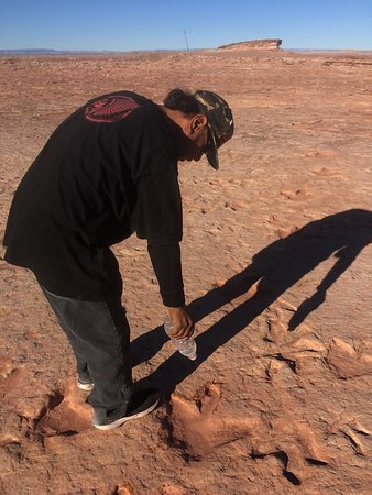 Tuba City, AZ: John, our Navajo guide. Highlighting the footprints with water.