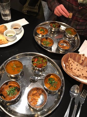Thali served on steel dishes.