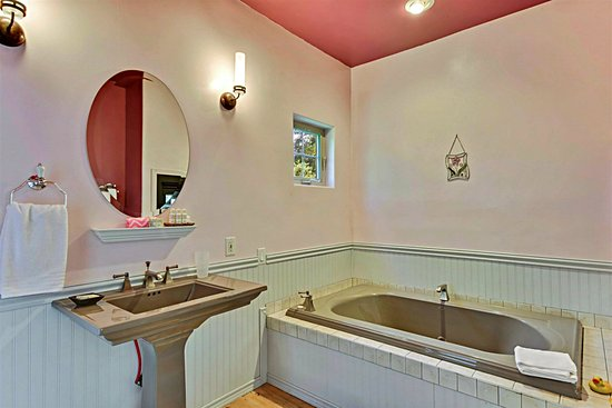 Fair Play Cottage sink & tub: notice the see-thru fireplace in the lower right of the mirror.