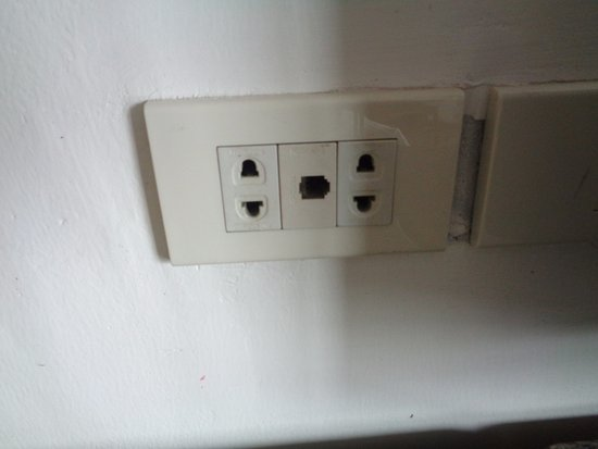 Royal Twins Palace Hotel: Old fashioned Thai electrical socket. Modern Thai appliances have 3 pins. I had to buy an adapto