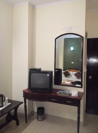 Hotel Delhi Darbar: A basic mirror in room with tv