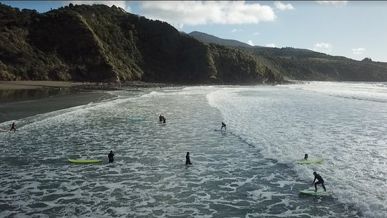 Raglan, Nueva Zelanda: An aerial view of the surf lesson with the beautiful backdrop of Mt. Karioi