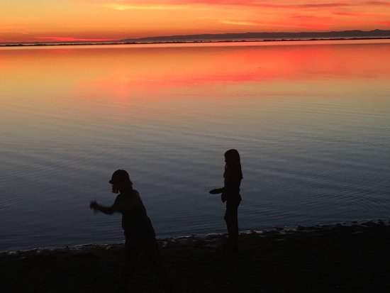 The kids skipping stones during sunset at the Cline Spit, Sequim WA