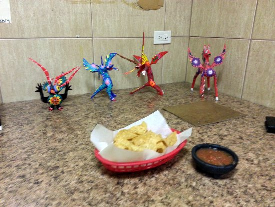 Mariachi's Tacos: counter seating with figures from Dia de los Muertos