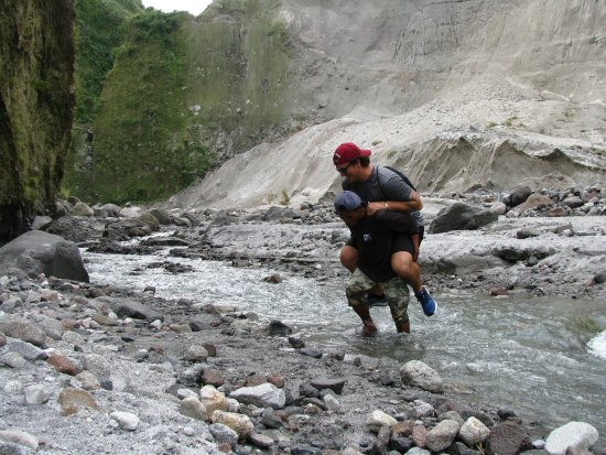 Capas, Philippines: The guide carrying my son over the creek