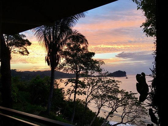 Arenas del Mar Beachfront & Rainforest Resort: Sunrise from our balcony with Manuel Antonio in the distance.