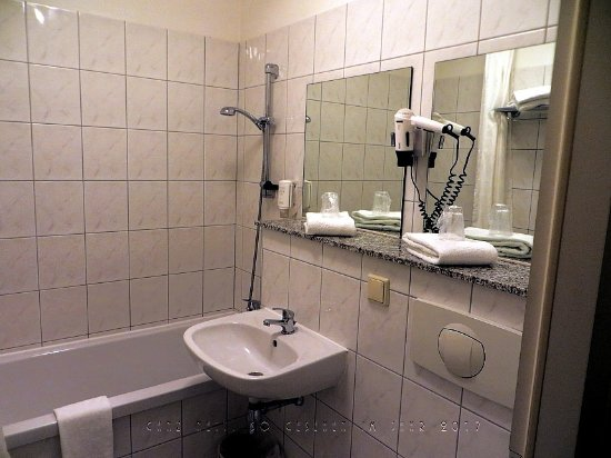 Blick ins Bad mit Badewanne, Dusche, Waschbecken, Ablage, Spiegel ...