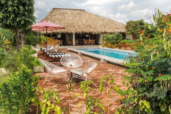 Tola, Nicaragua: Pool area with sun loungers, acapulco chairs and umbrellas facing our onsite restaurant La Canti