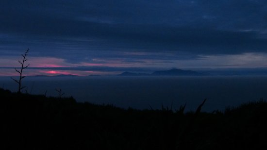 Bluff, Neuseeland: Sunset over Stewart Island, with sea fog rolling in.