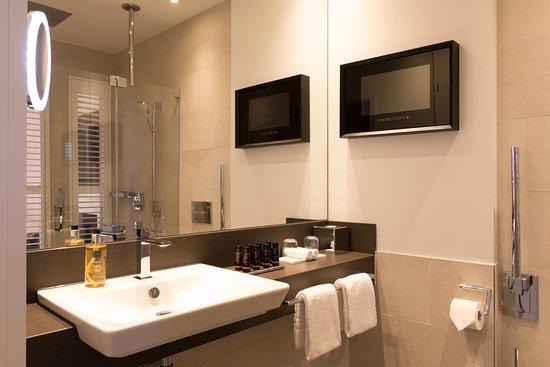 Badezimmer mit Fernseher und hochwertigen Kosmetikprodukten ...