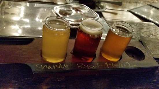 Buffalo Grove, IL: Flight of three beers with the container of spicy peanuts behind.