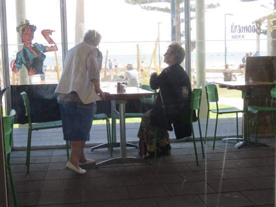 Glenelg, Australia: Veranda seating visible from inside the Cafe, playground and beach visible through the windows