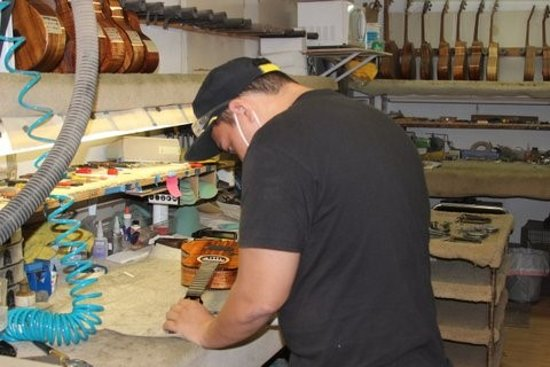 Kaneohe, HI: Kela works in Final Assembly carefully placing the bridge, tuners, nut, saddle and strings
