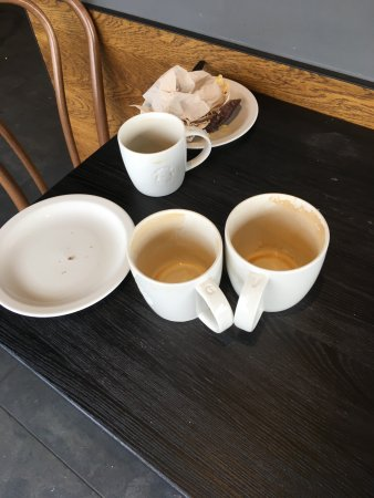 Honiton, UK: other tables had used cups and plates too.. 2/3rds of tables had used cups and plates on them.