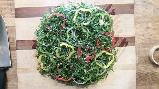 Vashon, WA: raw vegan pizza with 4 seed crust walnut basil pesto sunflower seed cheeze greens and basil