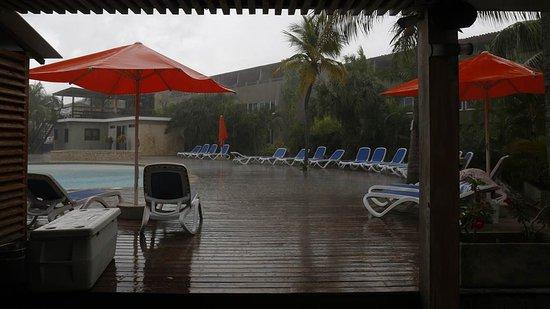 Eden Beach Resort: Uitzicht op het terras naast het zwembad vanaf de bar gezien (schuilend voor een tropische bui)