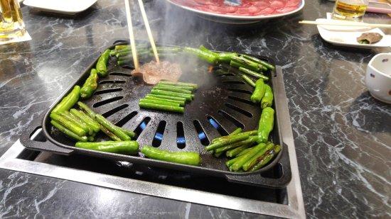 Akihiro-Tei: 先にニンニクの芽と獅子唐を焼いてから焼いた牛タンで包んで食します。