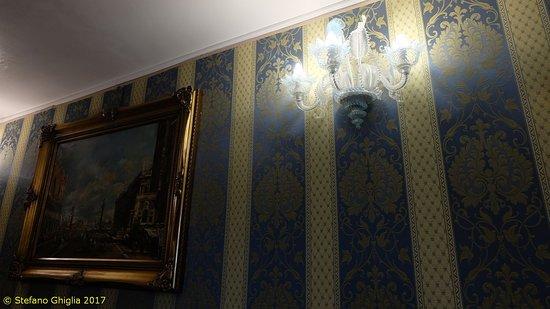 Dettaglio applique e pareti in tessuto damascato nella sala prima