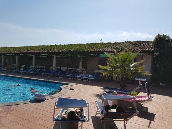 Etna Hotel: zwemabd met overdekte zone en achteraan de rook van de Etna