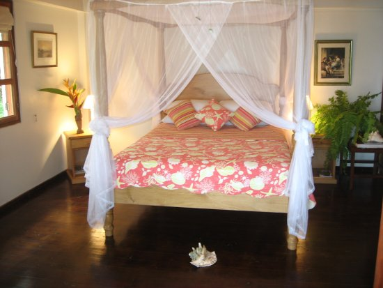 Petite Anse Beachfront Hotel & Restaurant Grenada: Almost all of our rooms feature four poster beds. Mosquitoes are rare due to the sea breeze.
