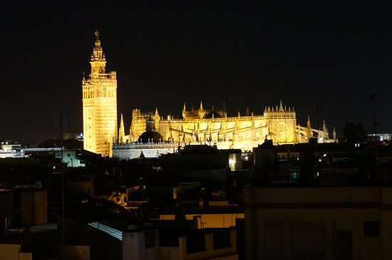 NIghttime view of Seville Cathedral from roof top terrace at Hotel Becquer.