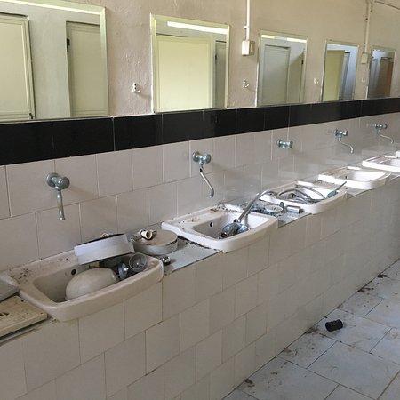 Villaggio Marinella: L'unico spazio assolato riservato alle tende, i vecchi bagni abbandonati e i lavelli per i piatt