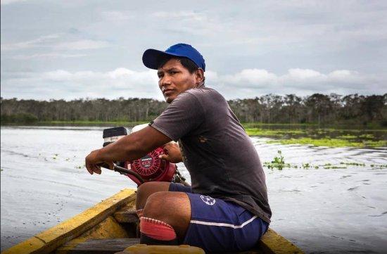 Tambopata Reserve Tours: Local family boat driver in Tambopata national reserve Peru