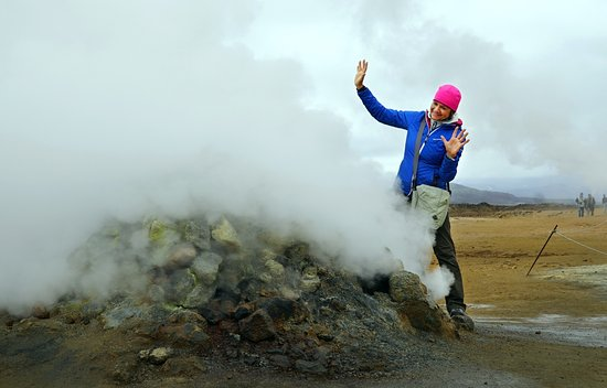 Hafnarfjordur, IJsland: Namaskard in Myvatn area - lady poses next to a fumarole.