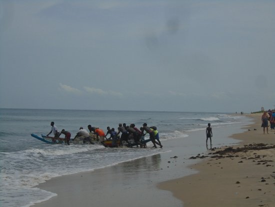 Kotu Beach: All hands to launch the fisherman canoe.