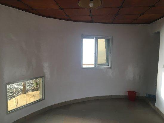 Roume, Guinea: Chambre d'un bungalow avec vue, par la fenetre hublot depuis le lit, sur la mer