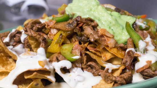 Mendota Heights, MN: Nachos Machos comes with grilled steak, beacon,  grilled onions, bell peppers, and cover with ch