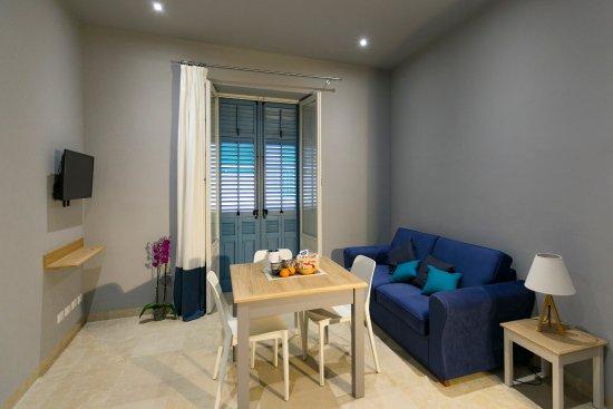 Il soggiorno ha arredamenti essenziali con un comodo divano, tavolo ...