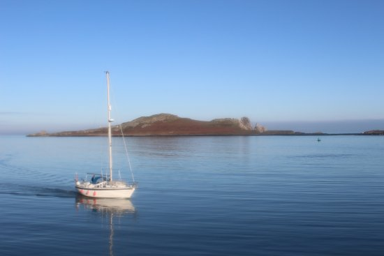 Howth, Ireland: Sail Boat crossing the path of Ireland's Eye