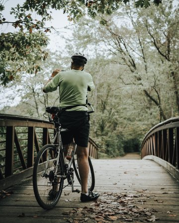 Felton, DE: Cyclist on the Pondside Nature Trail bridge